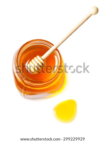 Honey in a glass jar with honey dipper isolated on white background close up. Fresh honey with a stick, macro. - stock photo