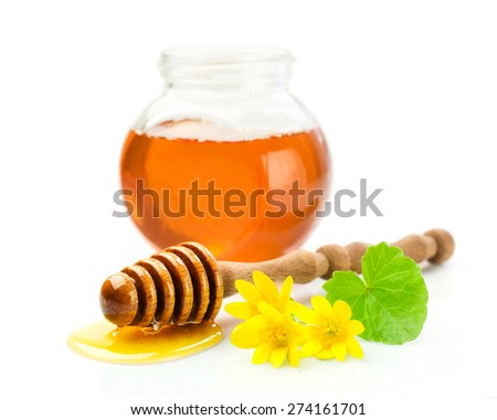 Honey in a glass jar with wooden dipper and flowers
