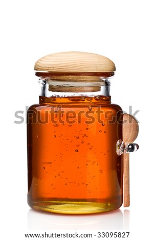 Honey in a glass jar with wooden spoon on side