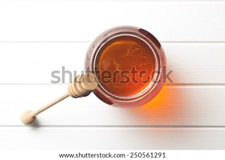 honey in a jar on kitchen table - stock photo