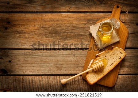 Honey in a jar, slice of bread and honey dipper on an old vintage planked wood table from above. Rural or rustic style breakfast concept. Background layout with free text space. - stock photo