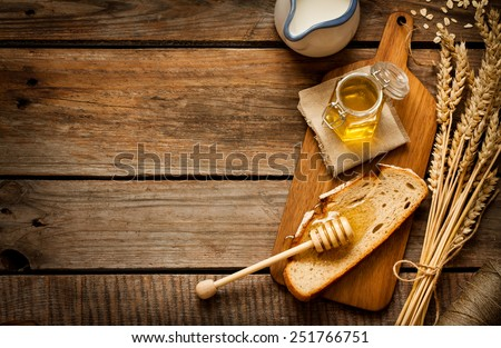 Honey in a jar, slice of bread, wheat and milk on an old vintage planked wood table from above. Rural or rustic style breakfast concept. Background layout with free text space. - stock photo