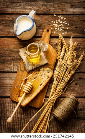 Honey in a jar, slice of bread, wheat and milk on an old vintage wood background from above. Rural or rustic style breakfast concept. - stock photo