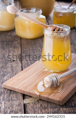 Honey in a jar with a wooden honey dipper. Other honey pots are on the background. - stock photo