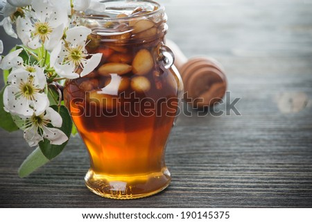 Honey in a jar with different nuts on a dark wooden table background - stock photo