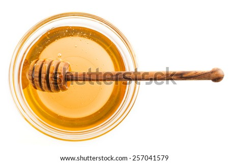 Honey in glass bowl with wooden dipping stick, isolated on white. - stock photo