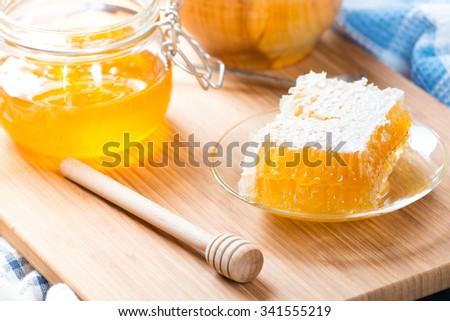 Honey in glass jar and honeycombs wax - stock photo