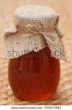 Honey in glass jar on textured surface - stock photo