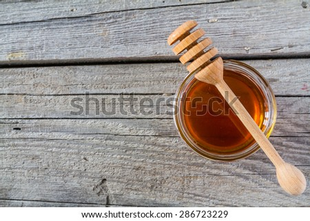 Honey in glass jar with wood dipper, rustic wood background, top view - stock photo