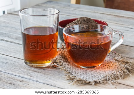 honey in glass, tea in cup on wooden table background.
