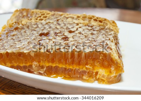 Honey in honeycomb in white plate on wooden table - stock photo