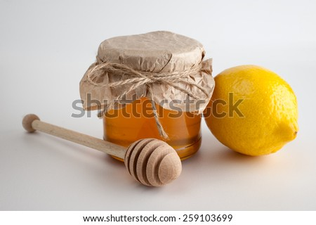 Honey in jar and lemon on a  white background - stock photo