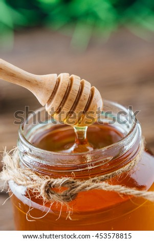 Honey in jar with wooden honey dipper on wooden table