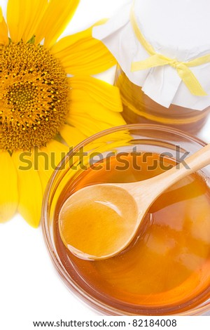 Honey in jar with wooden spoon and sunflower - stock photo