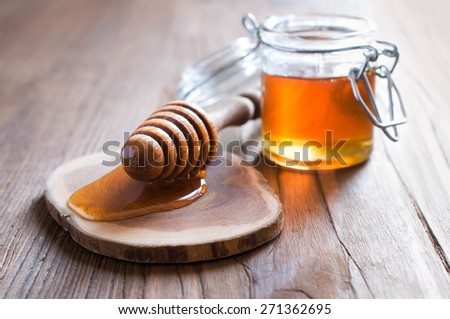 Honey in jur with wooden dipper in rustic style - stock photo