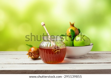 Honey jar and fresh apples with pomegranate over green bokeh background - stock photo