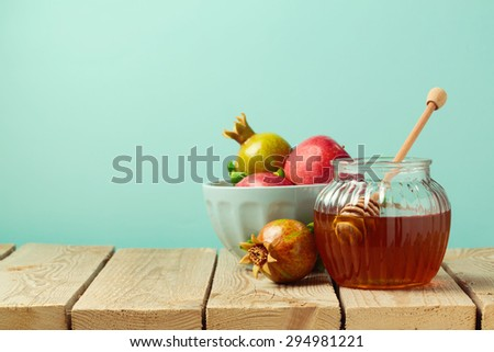 Honey jar and pomegranate on wooden table with copy space - stock photo