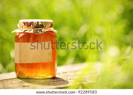 Honey jar with blank paper label on wooden table against green spring natural background - stock photo