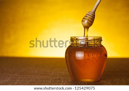 Honey jar with dipper and flowing honey, canvas background