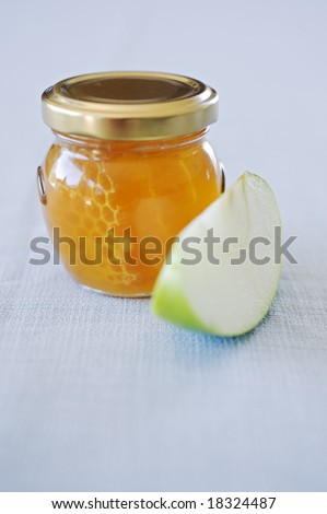 Honey jar with honeycomb and slice of green apple