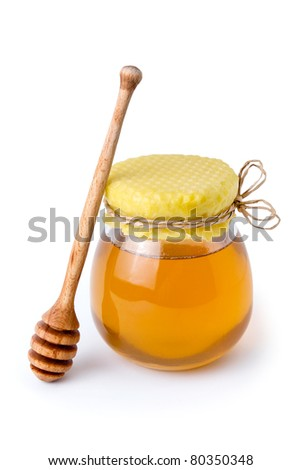 Honey jar with honeycomb lid and wooden dipper - stock photo