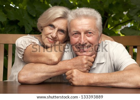 Honey older couple sitting at a table at home on the veranda - stock photo