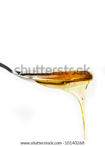 Honey on a spoon over a white background