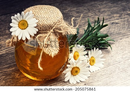 Honey pot with daisies on wooden table - stock photo