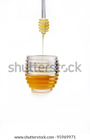 Honey pouring from drizzler into the bowl. Bowl is on a wooden t