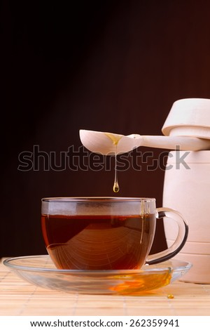 Honey pouring from drizzler into the bowl. Bowl is on a wooden table.