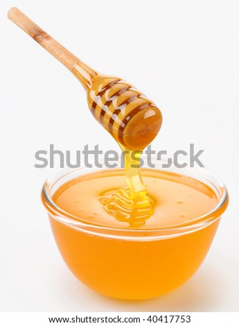 Honey pouring from stick to the bowl - stock photo