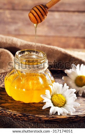 Honey pouring from wooden dipper in pot on tray with chamomile on sacking on wooden background - stock photo