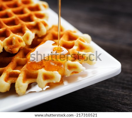Honey pouring on a fresh waffles. - stock photo