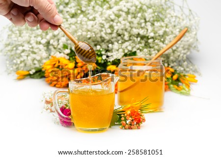 Honey pours in a jar from a stick hold by hand. Flowers are near and in background - stock photo