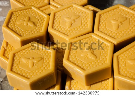 Honey soap in shape of honeycomb with decorative bee at farmers market. - stock photo