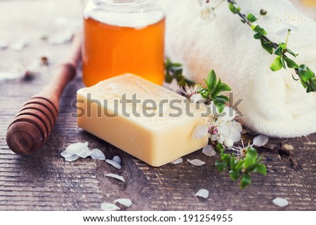 Honey spa. Bar of natural handmade soap, honey on wooden background. Selective focus.