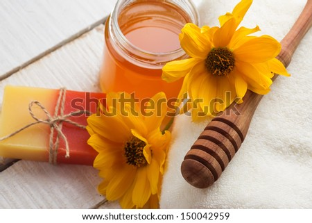 Honey spa. Handmade soap, flowers, towel on wooden background. Selective focus.