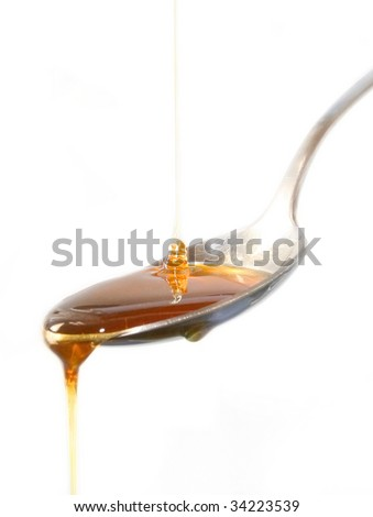 Honey spilling over the spoon