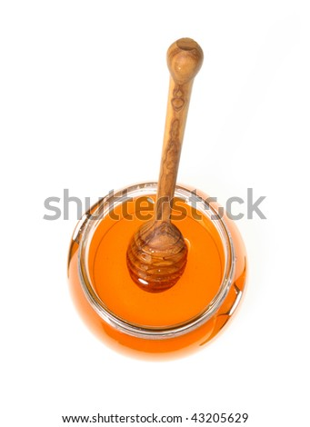 Honey spoon and the jar on white - stock photo