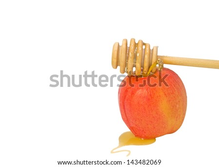 Honey stick and apple for Rosh Hashana.Symbol of the Jewish New Year.Sweet golden honey flowing over a wood stick on to a fresh red apple.Puddle of honey in the foreground.Isolated on white.Copy space - stock photo