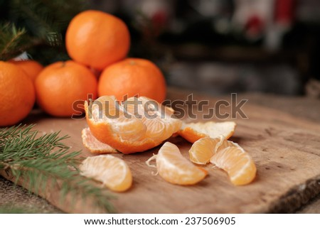 Honey tangerines whole and one peeled, on antique wooden table - stock photo
