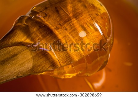 Honey with a wooden spoon close-up - stock photo