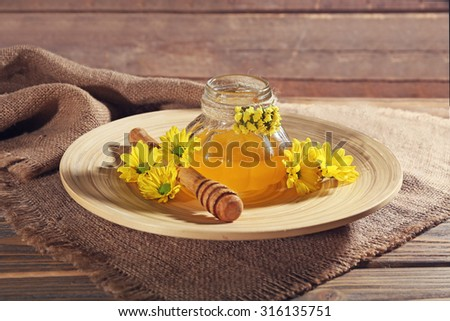 Honey with dipper and flowers on wooden table - stock photo