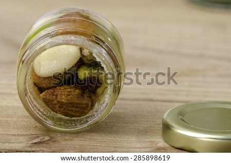 Honey with dried fruit and nuts, pistachio, almond, hazelnut over wood. - stock photo