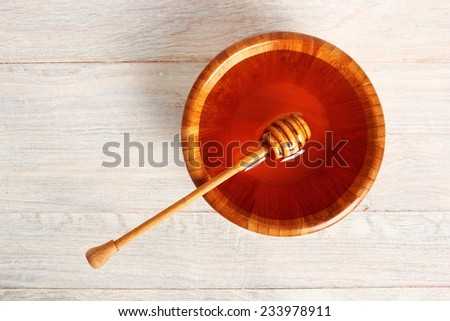 Honey with Honey Dipper in Wooden Bowl - stock photo