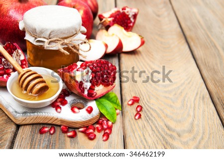 Honey with pomegranate and apples on a old wooden background - stock photo
