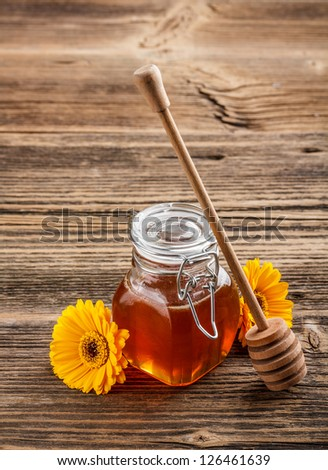 Honey with wood stick on vintage wooden background - stock photo