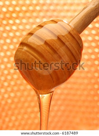 Honey with wood stick pouring. Honeycomb background
