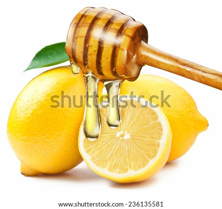 Honey with wood stick pouring onto a slice of lemon. White background. - stock photo