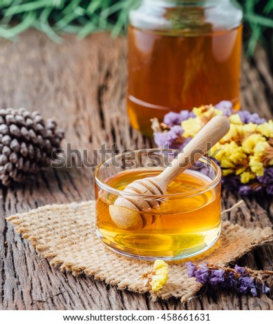 Honey with wooden honey dipper in small bowl on wooden table